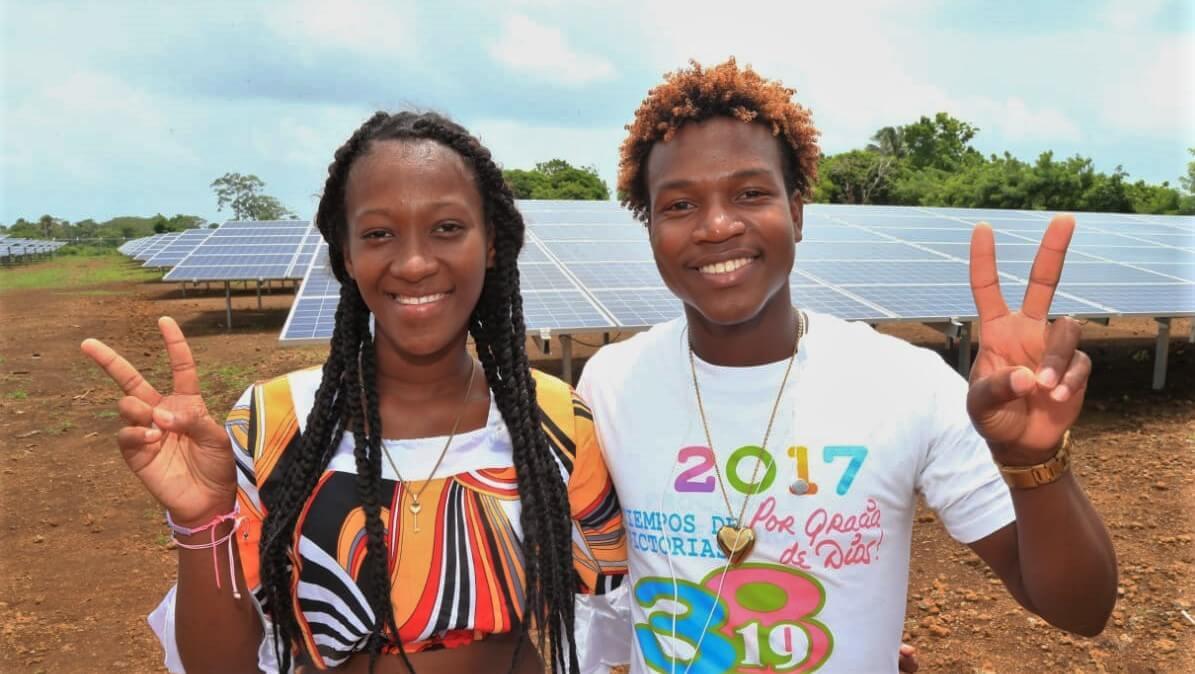 Pareja posa frente a un parque solar en Nicaragua. Electrificación rural